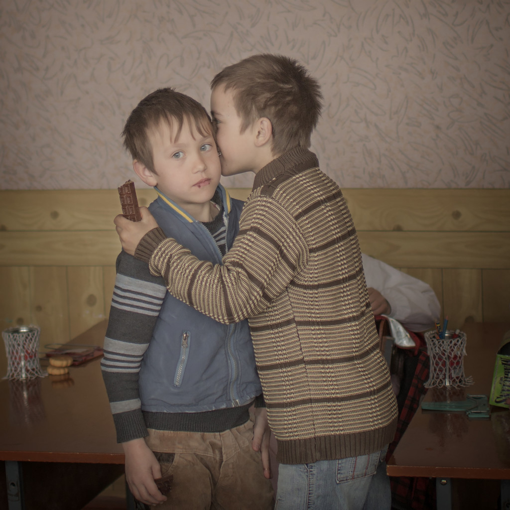 "140324  Igor and his friend Renat has an intimate moment of friendship in the classroom. Igor celebrates his ninth birthday and their grandmother bought chocolate for the the boys and their friends. ""I wish a pair of boxinggloves for my birthday, says Igor."" Igor also have a twinbrother and when they were only two years old their mother travelled to Moscow to work in the construction field. Three weeks later they found out that she died in a hemorrhage and they have no father. Thousands of children grow up without their parents in the Moldovan countryside. Some villages have turned into ghost towns. Young people have fled the country, leaving an dwindling, elderly population and young children. Schools are forced to close and whole villages are erased on the map. Some of them will never meet their parents again. For the children of Moldova, the future is uncertain."